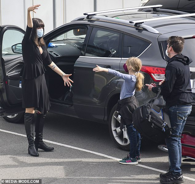 So close, yet so far: Tara Moss, 46, (left) was forced to give her husband Berndt Sellheim, 46, and daughter Sapphira, nine, (both right) an air-hug as they jetted into Sydney Airport from Canada amid the coronavirus pandemic on Wednesday