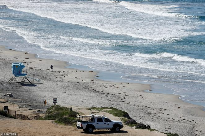 A lone person walks along the empty beach as a lifeguard keeps watch in San Diego, California on Tuesday