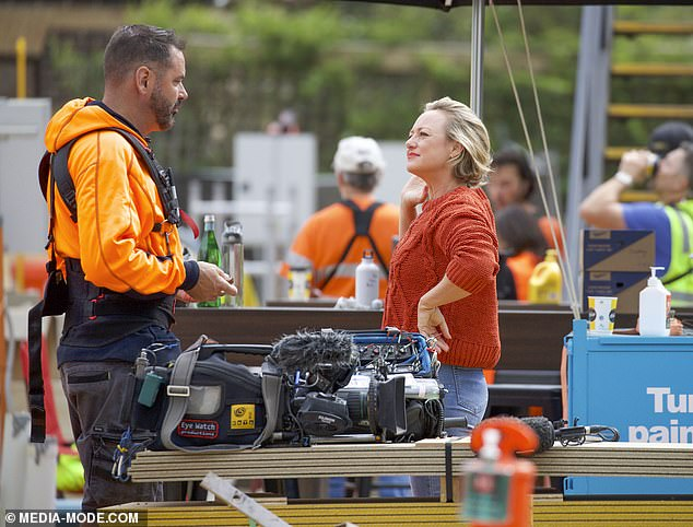 The show must go on! Shelley was spotted chatting a high-vis clad crew member