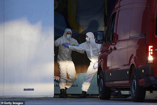 Members of Spain's Military Emergency Unit direct a van carrying bodies to be taken for cold storage at a makeshift morgue in a Madrid ice rink