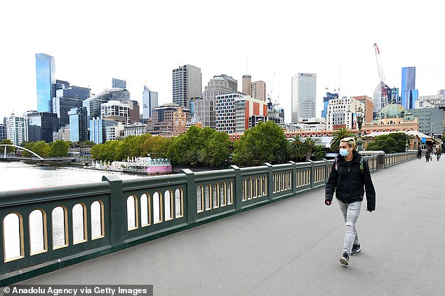 Ahead of the Prime Minister's announcement Victorian Premier Daniel Andrews outlined further restrictions were likely for Victoria (pictured: a man with a face mask walks the streets of Melbourne)
