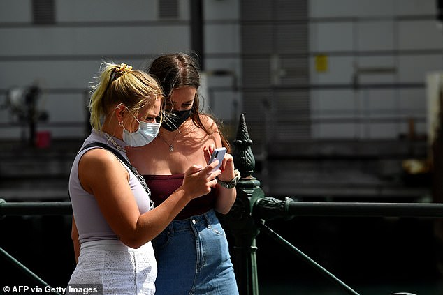 The Federal Government is scrambling to produce enough medical supplies as confirmed local coronavirus cases surge to more than 2,400. Pictured:Two young women in face masks walk along Circular Quay in Sydney on Wednesday