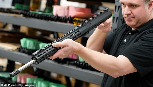 A worker inspects a finished AR-15 rifle barrel at Delta Team Tactical in Orem, Utah, this week