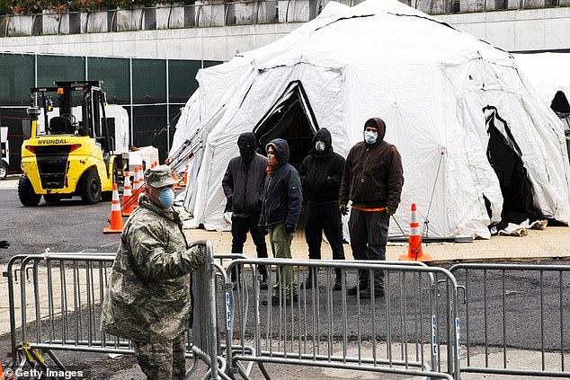 Вооруженные военнослужащие и медицинская инспекция Нью-Йорка установили белые палатки и рефрижераторы для импровизированного морга возле больницы Белвью в среду