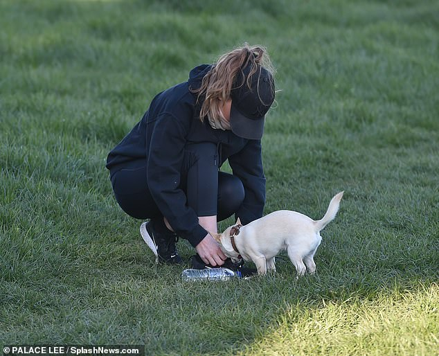 Cute: The stunner lavished attention on her dog as she got some fresh air amid the pandemic