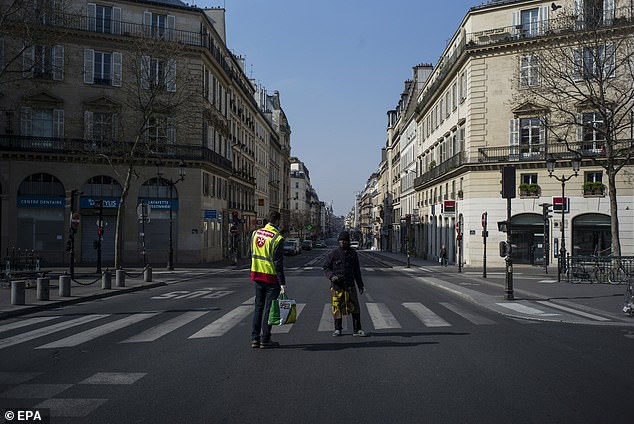 A volunteer of the Ordre de Malte ('Order of Malta'), the French branch of the Malteser International aid agency, speaks with a homeless person on a street in Paris, France, 27 March 2020. Since 17 March, all of France remains under a national lockdown