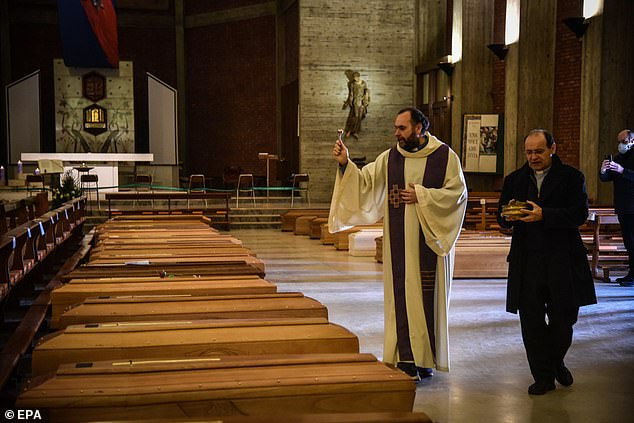 A priest blesses the coffins of the deceased inside the church of San Giuseppe in Seriate, Italy