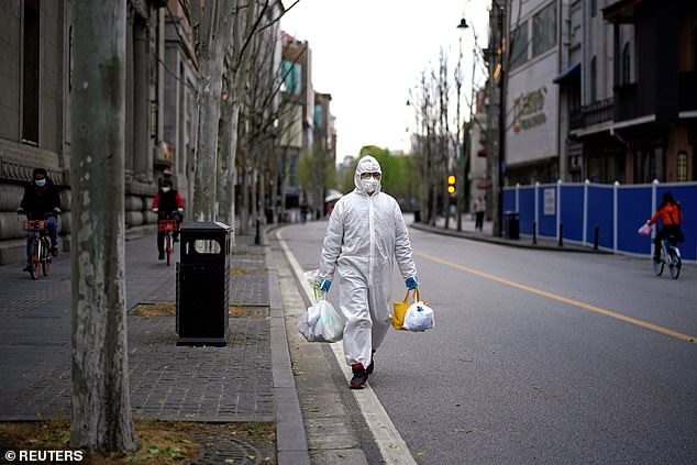 Deliveries of thousands of urns in Wuhan have raised doubts over China's official coronavirus death toll. Pictured: a man wearing a hazmat suit carries shopping bags in Wuhan