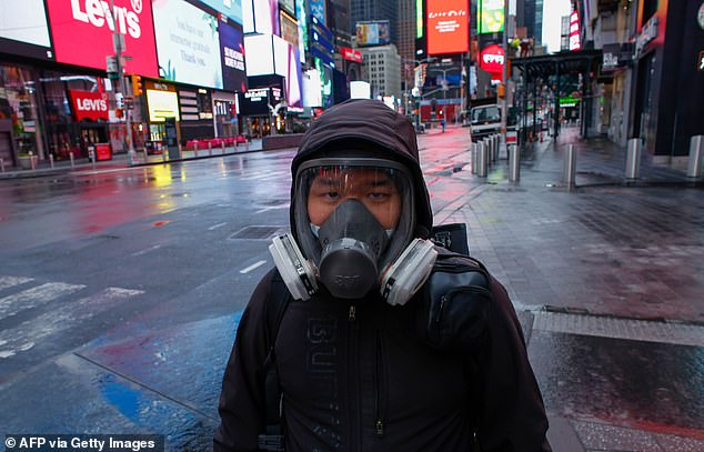 A man wears a face mask while he visits Times Square as rain falls on Saturday in New York City. Trump said on March 28, 2020 that he's considering a short-term quarantine of New York state, New Jersey, and parts of Connecticut