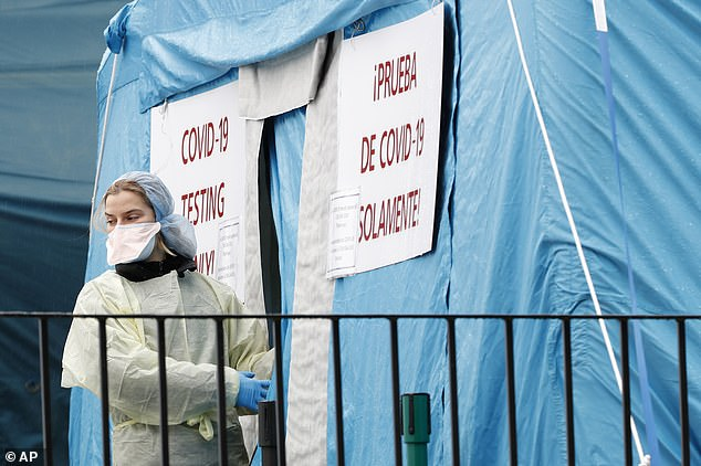 A medical worker prepares to reenter a COVID-19 testing tent set up outside Elmhurst Hospital Center in New York on Saturday. The hospital is caring for a high number of coronavirus patients in the city, and New York leads the nation in cases