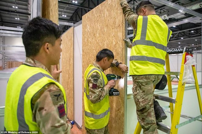 Soldiers help put up cubicles inside the new field hospital as the exhibition centre prepares for its first patients on April 4