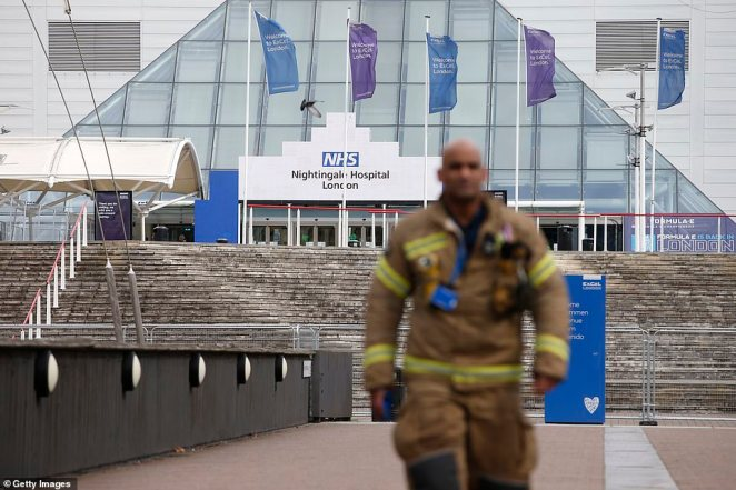 Pictured: A firefighter stands outside the new NHS Nightingale Hospital at ExCeL London, as the country tries to cope with the number of coronavirus patients