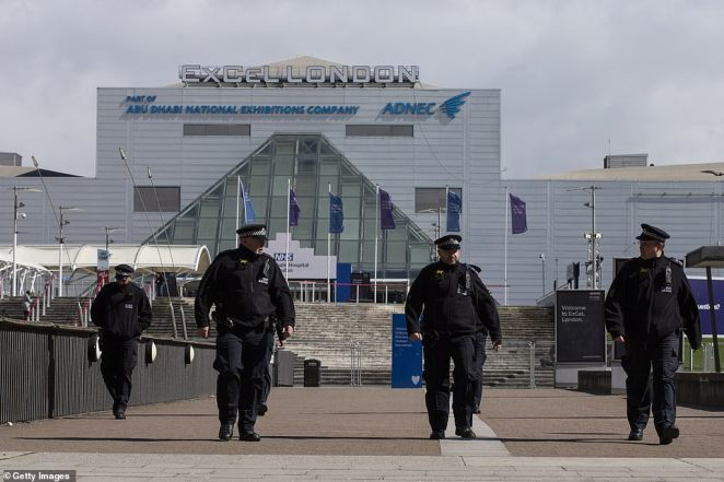 Staff from the Metropolitan Police officers stand outside the new NHS Nightingale Hospital as final preparation are made