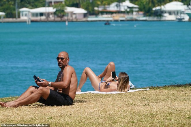 These two Floridians peak at their smartphones while taking in some sun in the Miami Beach section of Florida on Sunday