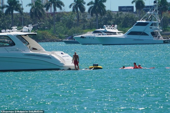 This boat owner tied a floating device to the back of his vessel while young kids enjoy themselves in the water