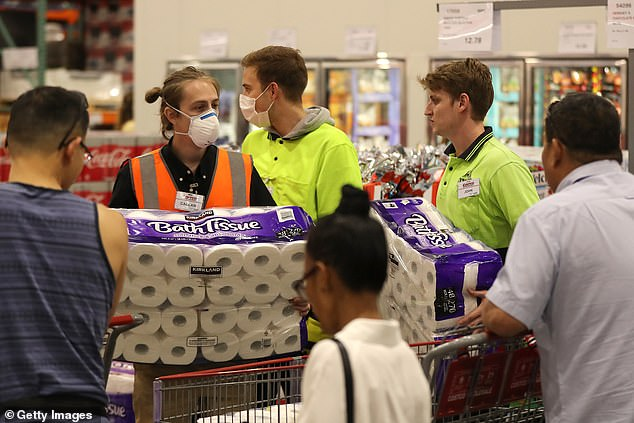 Staff members pictured wearing masks assist shoppers buying toilet paper at Costco Perth on March 19, 2020 in Australia