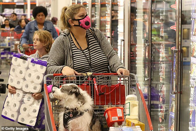 A shopper inspects the cold storage section with her dog in the trolley at Costco Perth on March 19, 2020 in Australia