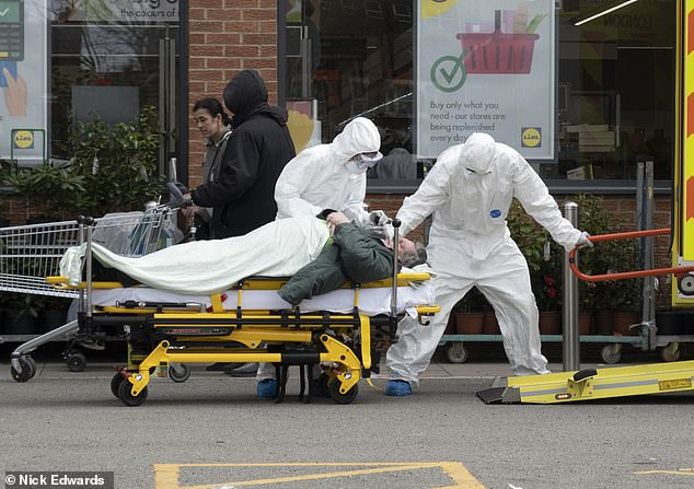 Despite the growing number of cases and deaths recorded overnight, Britain's coronavirus outbreak looks to be slowing down, leading experts said today. Pictured:  Paramedics in Hazmat suits take away a man that collapsed in a Lidl in South East London