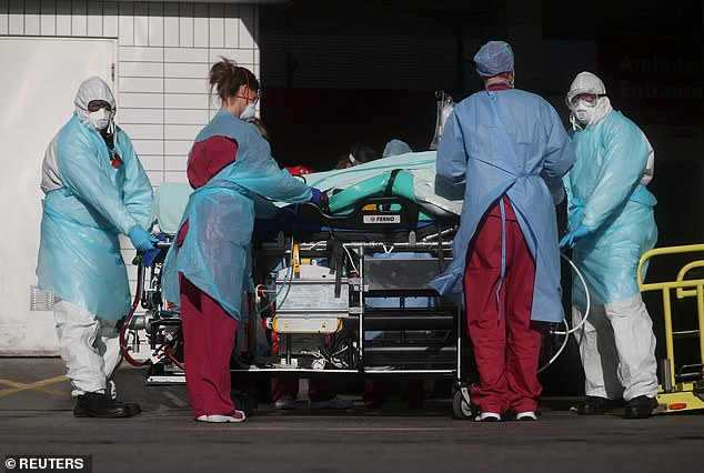 Medical staff are pictured wheeling a patient out of an ambulance at St Thomas' Hospital in London today. The capital city, home to around nine million people, is at the centre of the UK's crisis