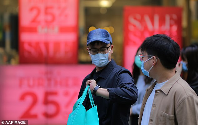 Two men wear protective face masks as they shop in a retail centre and walk past sale signs