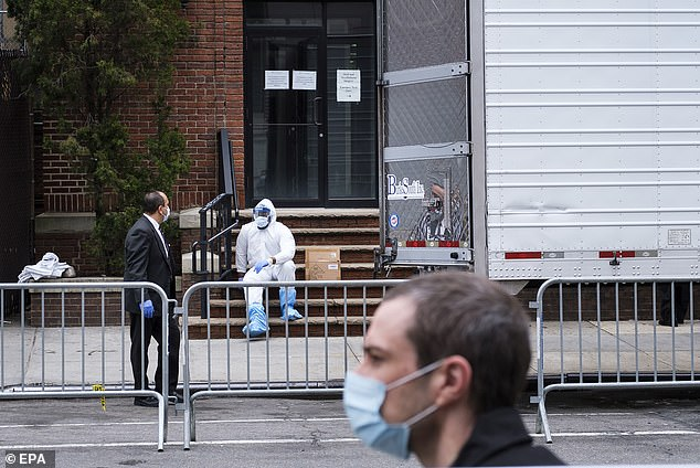 A hospital worker outside Brooklyn Hospital Center takes a break from loading bodies into a makeshift morgue on the street on Tuesday