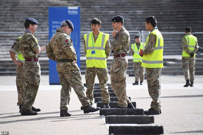 Pictured: British Army soldiers get instructions outside the ExCel center which is being turned in to a 4,000 bed temporary hospital for coronavirus patients in London, Tuesday, March 31, 2020