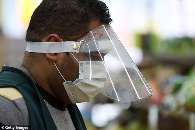 A Pat's Farms grocery store worker wears a mask and plastic visor on Tuesday in Merrick, New York.When masks aren't available, the CDC has advised health professionals to use some form of face shield that covers the entire front and sides of the face