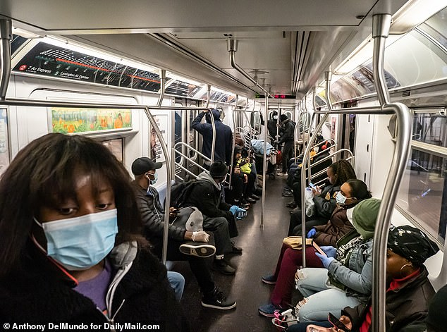 The coronavirus outbreak has prompted Americans to don surgical, cotton or even makeshift masks when they leave the home to buy groceries or exercise with the majority of the US now in various stages of lockdown due to the pandemic. Pictured above is the New York subway on Tuesday