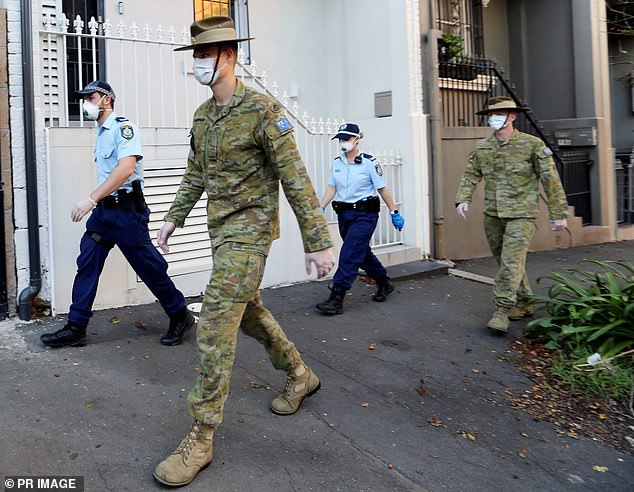 Australian Defence Force officers donning face masks have accompanied police for door knocks