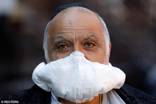 Others resort to making masks from household items. A man is seen using a diaper as a makeshift facial mask in Brooklyn, New York City