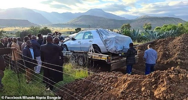 Funeral guests seen here watchingChief Pitso's Mercedes Benz being lowered into the 'grave'