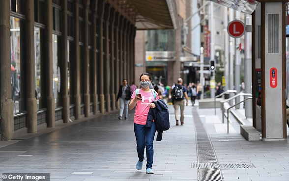 Face masks have become a regular sight in Australia, with people wearing them to protect from the virus (pictured, a woman in Sydney on March 17)