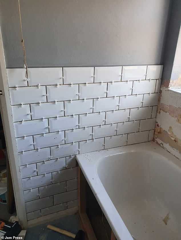 She used a ready-made tile adhesive costing £20 and a grey grouting kit at £18 in order to redo the tiles from the bathroom (pictured during the renovation work)