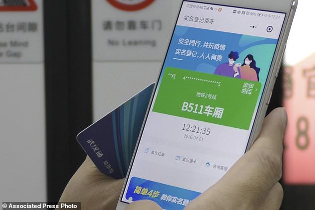 A passenger holds up a green pass on their phone on a subway train in Wuhan in central China's Hubei province. Green is the 'health code' that says a user is symptom-free and it's required to board a subway, check into a hotel or just enter Wuhan