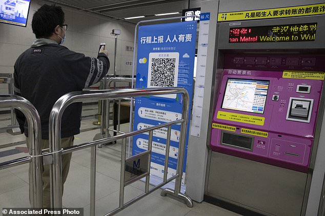 China has faced widespread doubts and criticism over its use of artificial intelligence to monitor its citizens during the pandemic. A passenger is pictured scanning a QR code to get his green pass at a subway station in Wuhan on this file picture taken on April 1