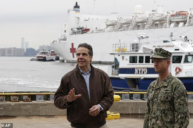 Andrew Cuomo, left, gestures during a brief press conference as he stands next to a rear admiral.John B. Austin as USNS Comfort, a naval hospital ship with a capacity for 1,000 beds, goes to Pier 90 in New York on Monday. Ship criticized for accepting only 20 patients