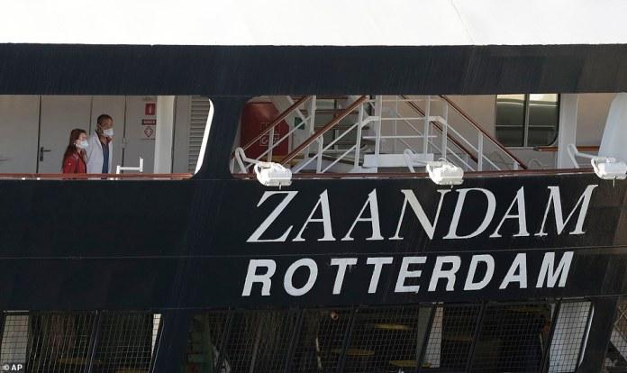 Yesterday morning, two people on MS Zaandam wearing masks watch from its bridges