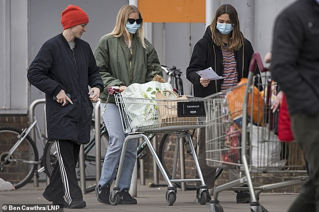 Buyers wearing face masks line up to enter Sainsbury's supermarket on Ladbroke Grove in West London on Wednesday