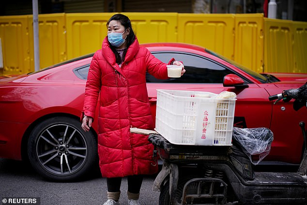 Doubts have been raised over Beijing's honesty and transparency for its official figures about the coronavirus outbreak.A vendor wearing a face mask is pictured selling soup today on a street at a residential area blocked by barriers in Wuhan, where the pandemic first emerged