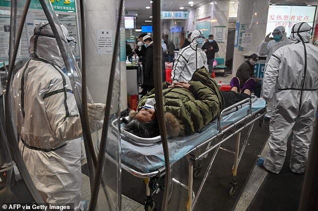 Medical staff members wearing protective clothing to help stop the spread of a deadly virus which began in the city, arrive with a patient at the Wuhan Red Cross Hospital in Wuhan