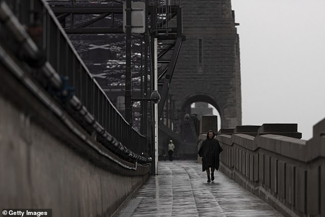 A man walks across the Sydney Harbour Bridge in heavy rain during the state wide lockdown