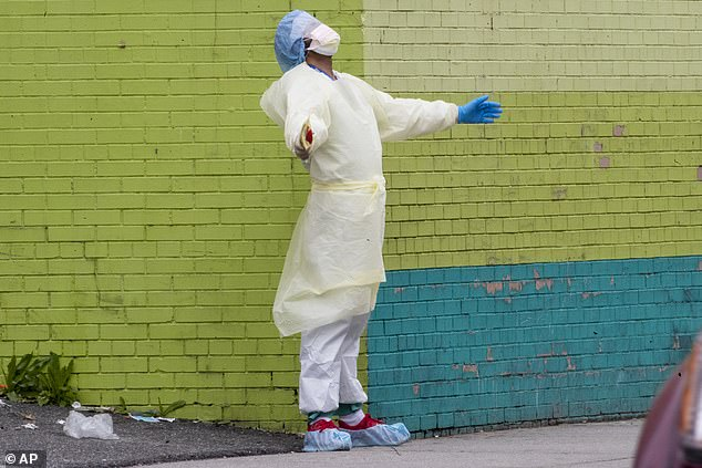A medic of the Elmhurst Hospital Center medical team reacts after stepping outside of the emergency room on Saturday in Queens, New York City