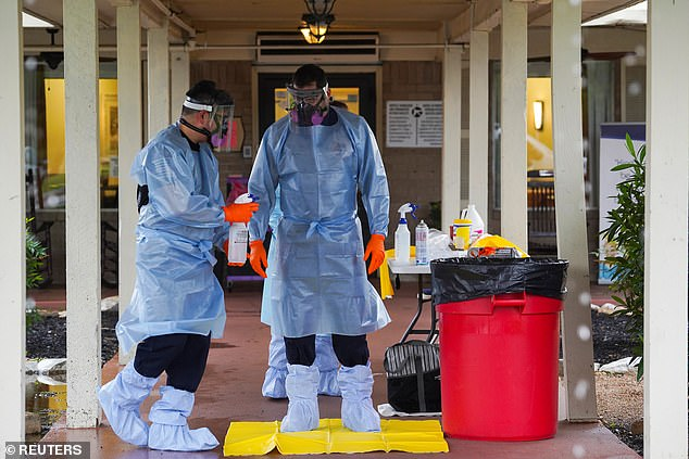 Emergency responders in protective gears disinfect themselves at the Southeast Nursing and Rehabilitation Center nursing home, where many residents and employees has been infected with coronavirus disease, in San Antonio, Texas on Saturday