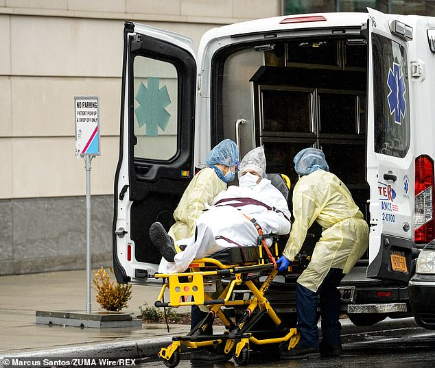 EMTs take a coronavirus patient to the hospital at Queens Mount Sinai Hospital on Friday