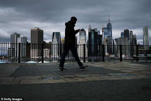 The Manhattan skyline stands in the distance as people try to get some time outside in Brooklyn on Saturday in New York City