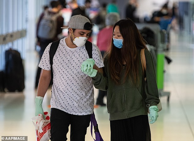 Pictured: couple holding hands at Sydney International Airport on March 27. The initial positive effect of the social distancing measures on the virus' spread could mean they stay in place for longer