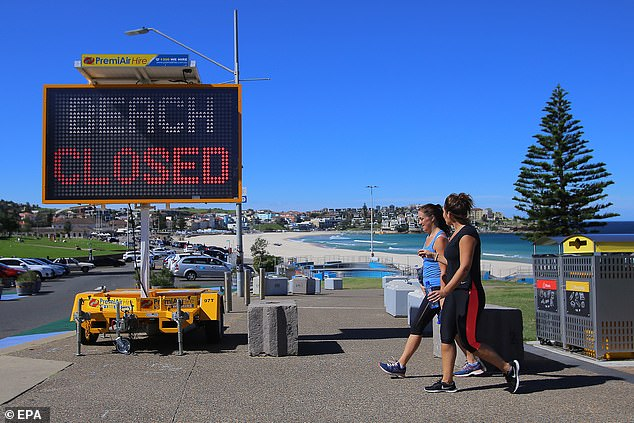 Two women walk in front of a 'beach closed' sign at Bondi Beach on Saturday. Australians have been warned coronavirus social distancing measures may last until after Christmas