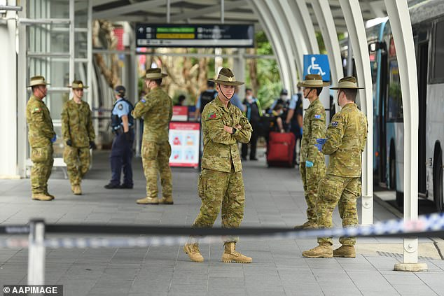 Army personnel wait for travellers to take them to hotels for quarantine after returning from overseas