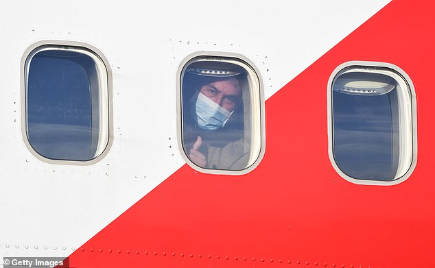 A passenger wearing a face mask gives a thumbs up on arrival in Sydney from Santiago on March 29