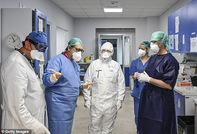 More than 100 doctors have died from coronaviruses in Italy while many are battling the trauma of seeing their colleagues die. Pictured: doctors at Cannizzaro hospital